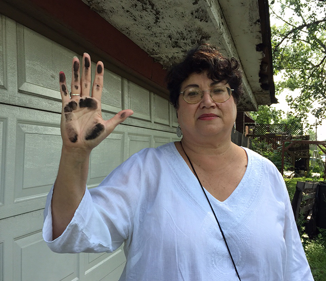 Environmental activist Peggy Salazar holds up a sooty hand after wiping it across a garage across the street from a petcoke storage facility on Chicago's Southeast Side. (Photo by Robin Amer)